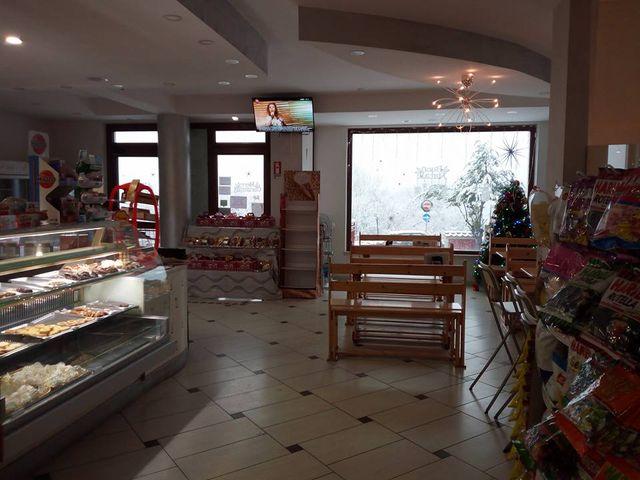 Interno della pasticceria Sale, Zucchero e Caffè: vetrine con dolci sulla sinistra e sulla destra delle panchine in legno