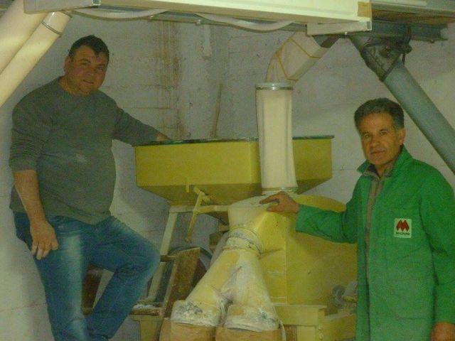 Un uomo mentre versa il grano dentro un contenitore del mulino per farina
