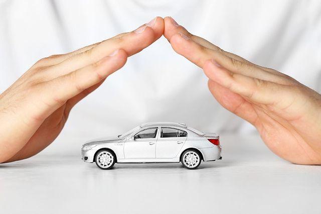 modellino di auto con sopra le mani giunte di una persona