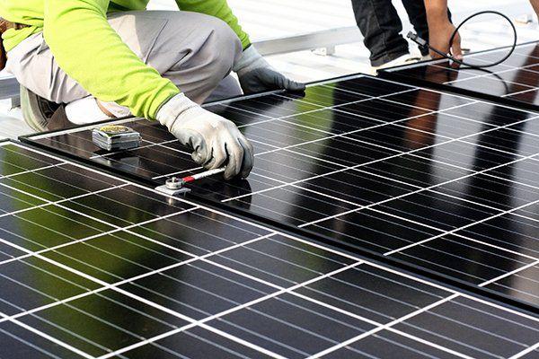 una mano di un tecnico e dei pannelli solari