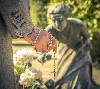 Mano che regge un rosario