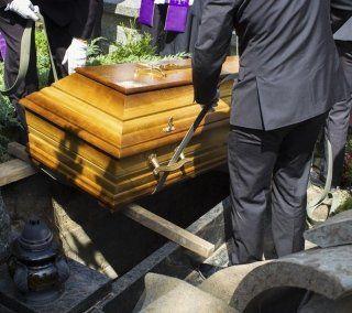 Personale funerario che posa una bara in una fossa