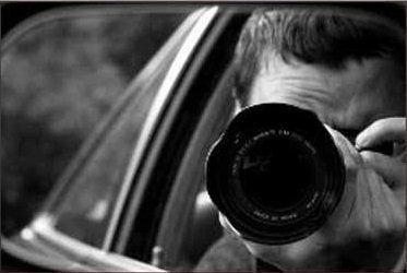 detective privato che scatta fotografie con un obiettivo potente