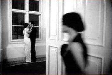 Donna che dietro la porta vede una coppia che si bacia
