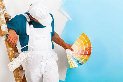 operaio che pittura un muro con dei colori in mano