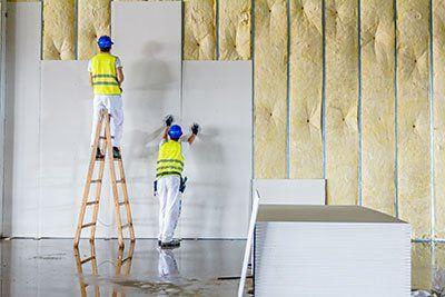 operai che lavorano su un muro uno su una scala e uno regge dei pannelli