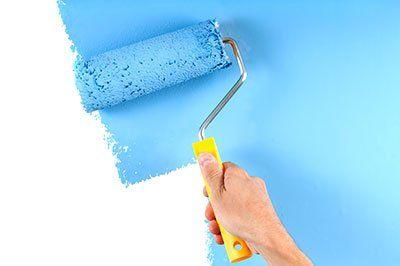 una mano che vernicia di blu un muro con un rullo