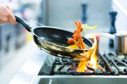 Chef cuoce una pietanza in padella