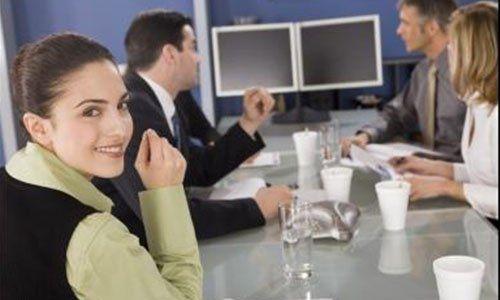 delle persone alla scrivania che discutono in un meeting e una donna sorridente in posa per una foto