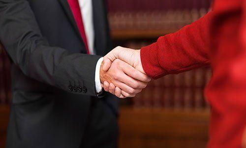 vista di una stretta di mano tra un uomo in giacca e cravatta e una donna con un tailleur rosso vista di spalle