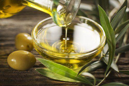 primo piano di una bottiglia mentre si versa olio di oliva vergine in una ciotola