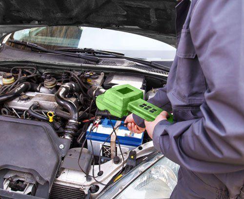 una mano con in mano un dispositivo diagnostico e dietro vista di una macchina con il cofano aperto