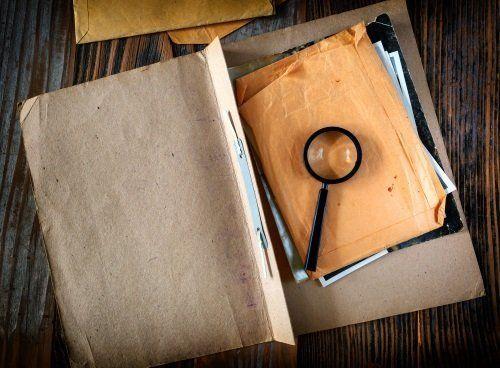 un raccoglitore aperto e una lente di ingrandimento appoggiata su una busta