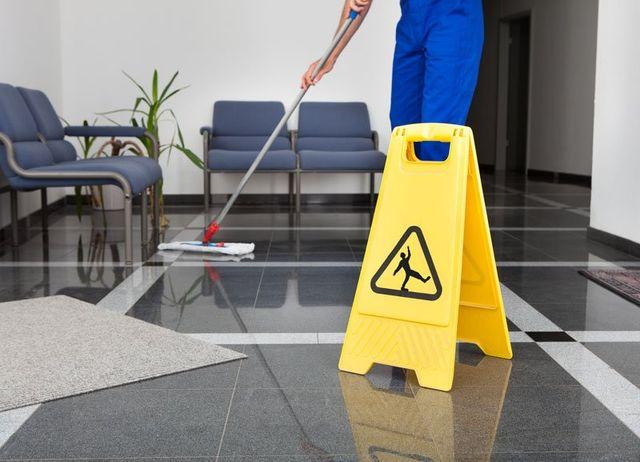 un uomo sta pulendo per terra con un mocio e accanto un cartello giallo che avvisa la possibilita' di cadere