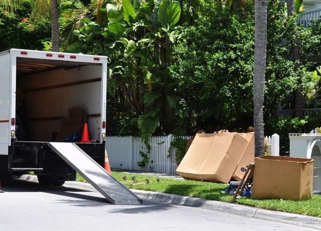 un camion dei traslochi con il rimorchio aperto e degli scatoloni sul ciglio della strada