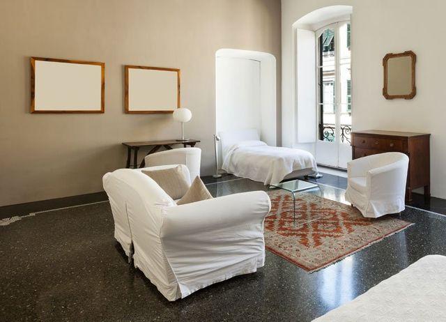 camera da letto con poltrone bianche un tavolino di vetro e si intravede il letto