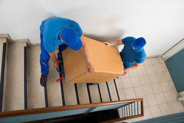 men lifitng a big box thru the stairs
