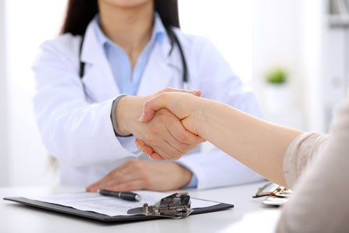 Female doctor shaking hand with patient in Hernando