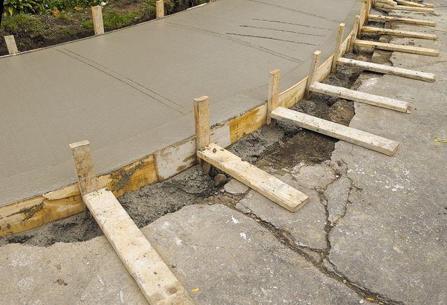 Spreading concrete for sidewalk repair