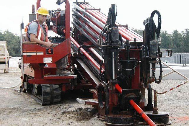Big drill operating on dirt mound