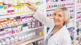 una farmacista vicino a uno scaffale di medicine