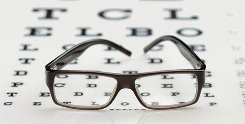 occhiali da vista appoggiati sopra uno schermo per visite oculistiche