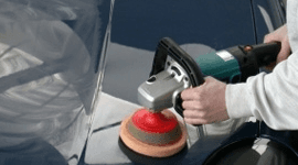 Operaio che pulisce il cofano dell'automobile