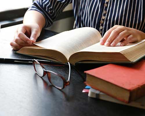 una ragazza alla scrivania con un libro aperto e accanto degli occhiali