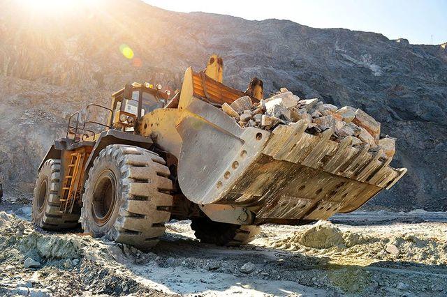 Macchina escavatore con la pala piena di pietre