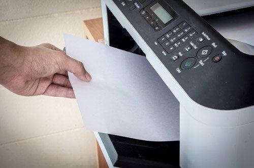mano che ritira un foglio da una stampante