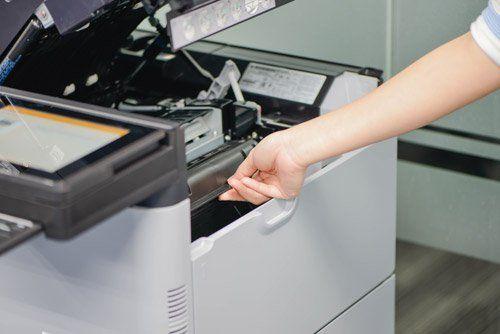 mano di una donna che tira lo sportello di una stampante fotocopiatrice