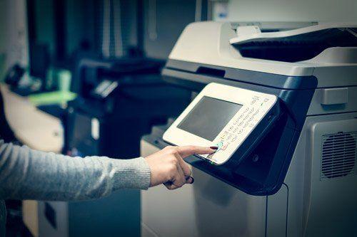 donna che clicca il pulsante invio della stampante