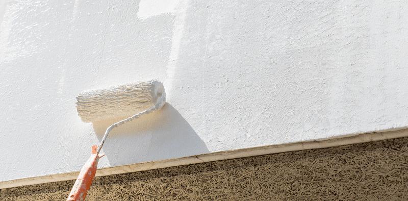 un rullo con della vernice bianca appoggiato su un pannello bianco a muro