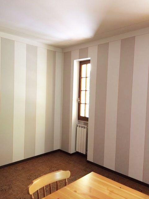 un'imbiancatura a strisce in una stanza con una piccola finestra in legno e un tavolo e una sedia di legno che si intravedono