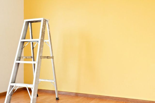 una scala di ferro e una parete imbiancata di color giallo