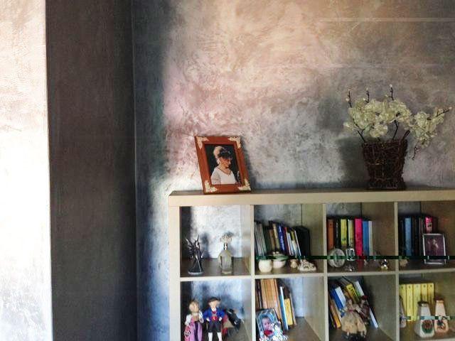 una parete grigia a sfumature bianche e un armadio con sopra una foto dentro a una cornice, un vaso di paglia di fiori artificiali e sotto altri oggetti