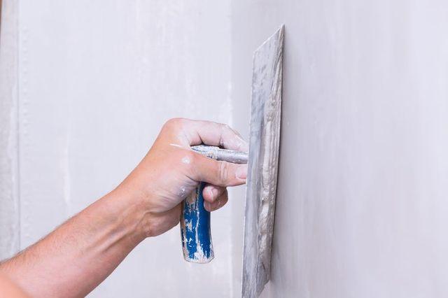 una mano che impugna una spatola durante una lavorazione su un muro grigio