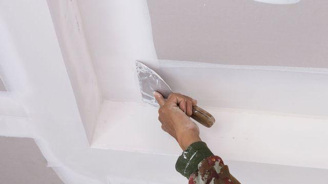 una mano con in mano una spatola vicino a un muro