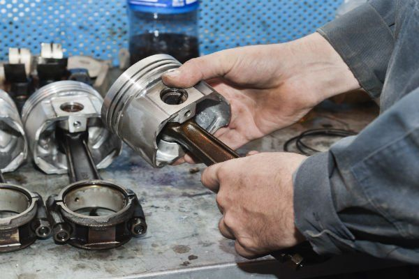 The mechanic holds the piston in hand before repair.