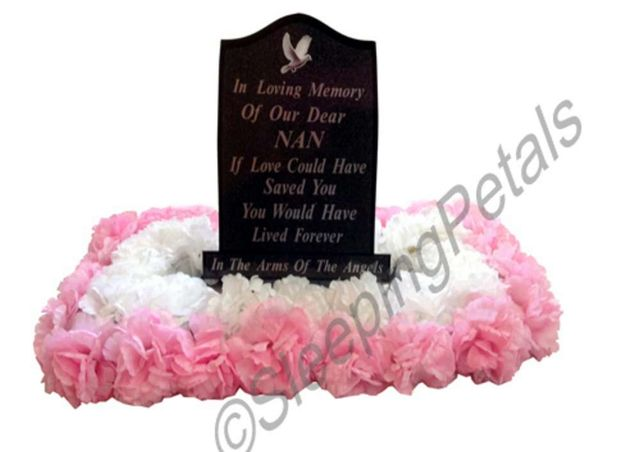 White and pink artificial flowers that surround the headstone