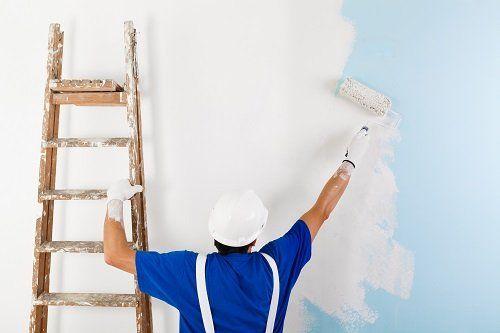 Uomo dipinge  la parete di bianco con rullo sostenendo una scala