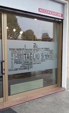 vista laterale di portone in vetro di acconciature salone con vetrofanie