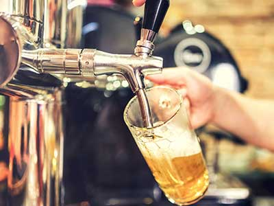 una mano che riempie un bicchiere di birra da un rubinetto