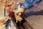 removing leaves from gutters on a house