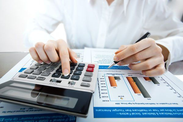 Accountant working on accounts by using calculator