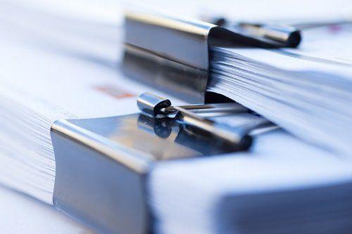 Documenti raccolti con una pinza di metallo
