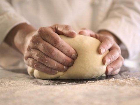 Due mani impastano la base delle pizze in una tavola con farina