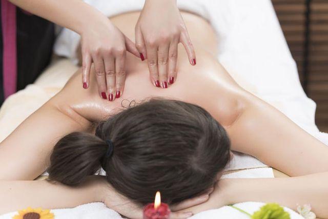 due mani di una donna che fa un massaggio alla schiena a una ragazza sdraiata