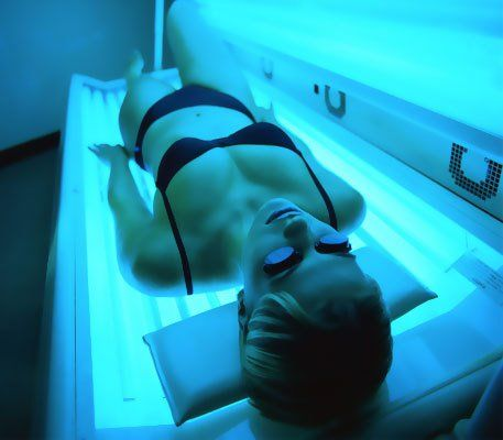 A lady in a black bikini and protective goggles, lying on a sun bed
