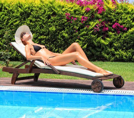 A tanned lady in a black bikini and white sunhat, lying on a lounger beside a pool